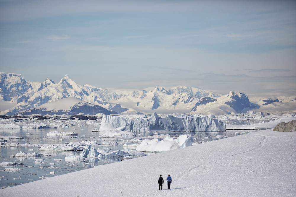 Expedition cruise ship passengers enjoy a hike in the beautiful snow in Antarctica.