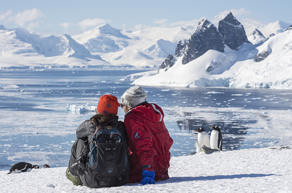 Small ship expedition cruise passengers enjoy the views of Antarctica and Gentoo penguins.